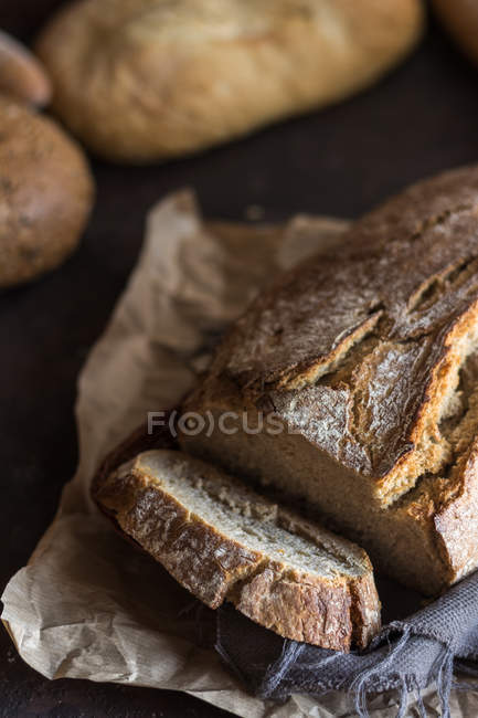 High angle of sliced home-made bread on bakery paper. — Stock Photo