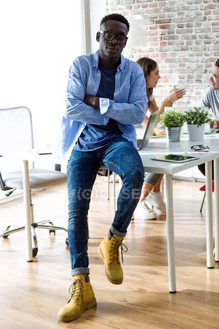 Retrato de jovem empresário apoiando-se na mesa e olhando para a câmera — Fotografia de Stock