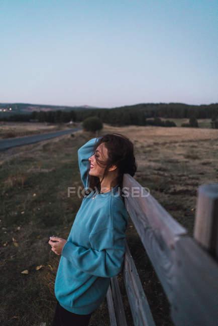 Seitenansicht eines Mädchens in blauem Sweatshirt, das sich am Zaun auf dem Land lehnt — Stockfoto