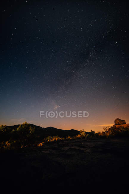 Landscape with mountain silhouettes and milky way in night sky — Stock Photo
