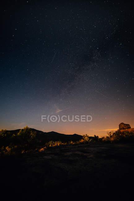 Paisagem com montanha silhuetas e a Via Láctea no céu noturno — Fotografia de Stock