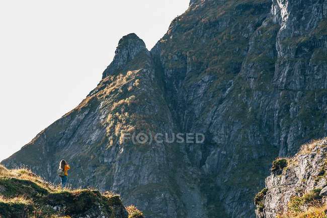 Rear view of woman with backpack standing on cliff and enjoying mountains view — Stock Photo