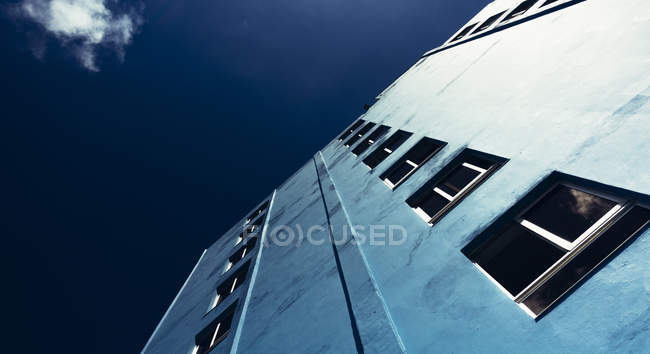 High angle view of building wall with windows on background of blue sky. — Stock Photo