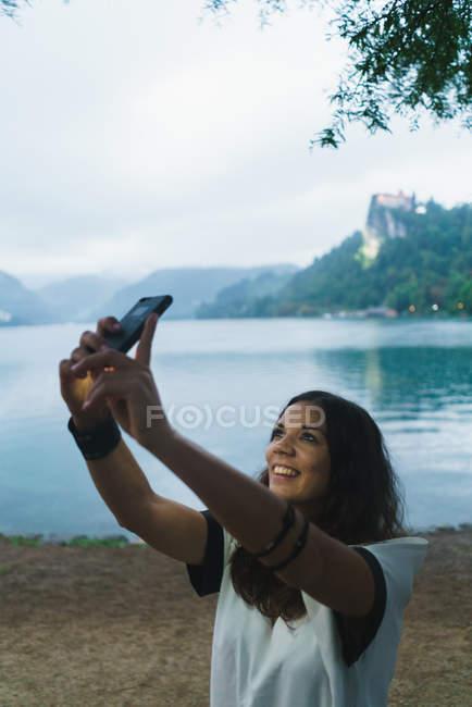 Lächelnde Brünette Frau nehmen Selfie am Seeufer — Stockfoto