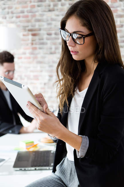 Portrait of  young businesswoman sitting on table and using digital tablet. — Stock Photo