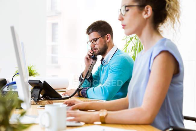 Вид збоку бізнесмен можете відповісти на телефонний дзвінок на робочому місці в сучасні офісні. — стокове фото