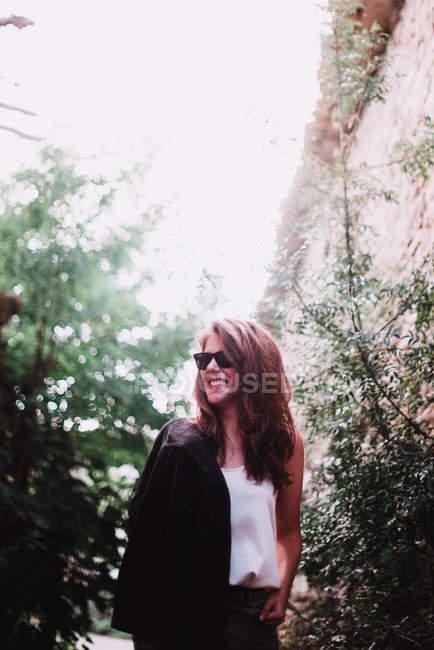 Portrait of smiling brunette girl in sunglasses posing in forest — Stock Photo