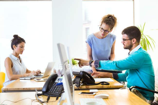 Vue latérale des gens d'affaires travaillant dans un bureau moderne . — Photo de stock