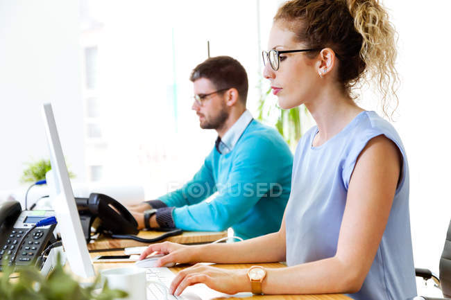 Side view of young people working in modern office. — Stock Photo