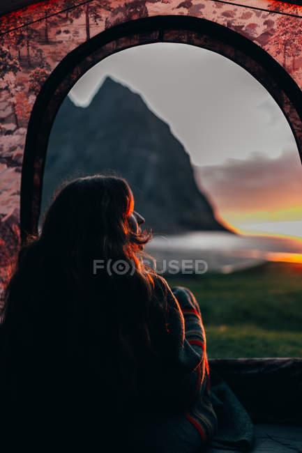 Vista traseira da mulher iluminada pelo sol, enrolada num cobertor aqui na tenda e apreciando o belo pôr do sol. — Fotografia de Stock