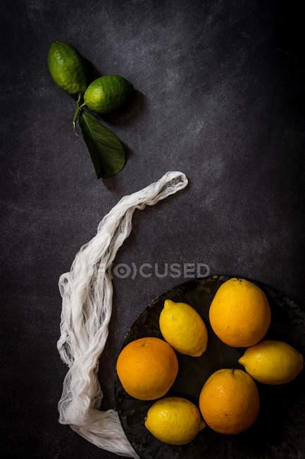 Stillleben mit frischen Zitronen und Orangen auf dunklen Tisch — Stockfoto