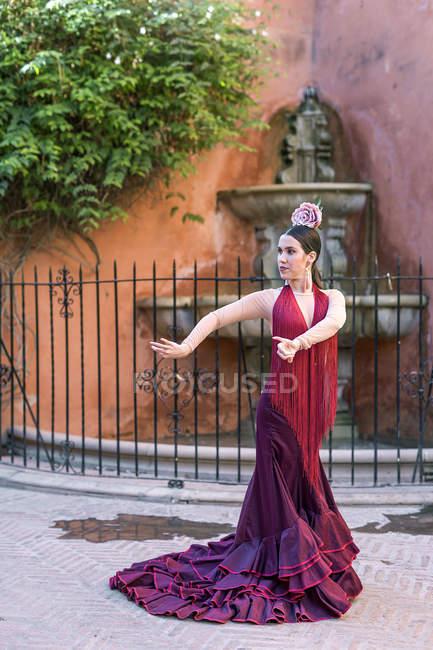 Фламенко, танцівниця носіння типовий латиноамериканського костюм позують над вулиці фонтан на тлі — стокове фото