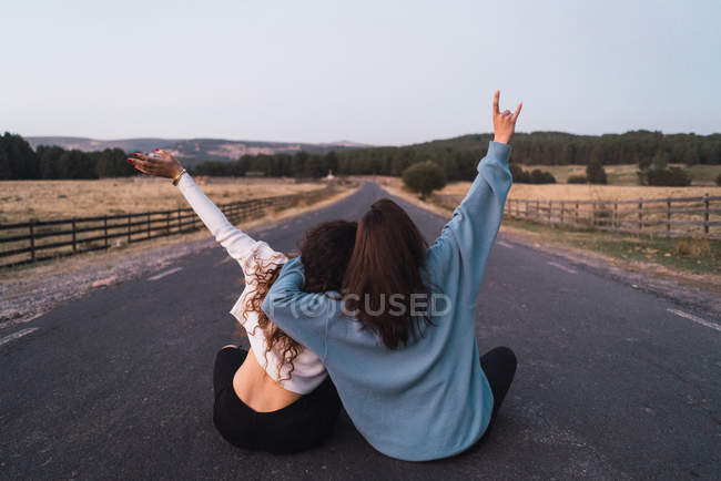 Задний вид на двух женщин, сидящих посреди дороги — стоковое фото