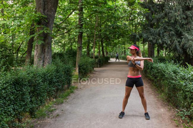 Fille échauffement avant jogging à parc ruelle — Photo de stock