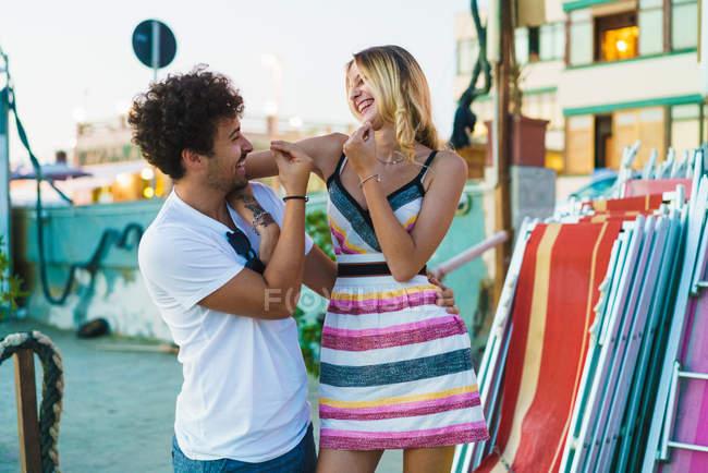 Retrato de jovens alegres e olhando uns aos outros com sorriso e gesticulando na cena de rua — Fotografia de Stock