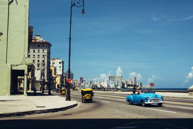 Cuba - 27 agosto 2016: Vista di retro automobile sulla strada della vecchia città costiera sotto cielo blu — Foto stock
