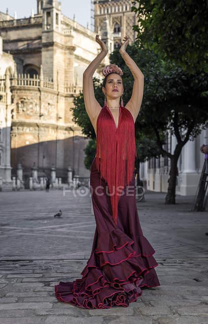 Danseuse de flamenco portant un costume national posant sur la place de la ville avec les bras levés — Photo de stock