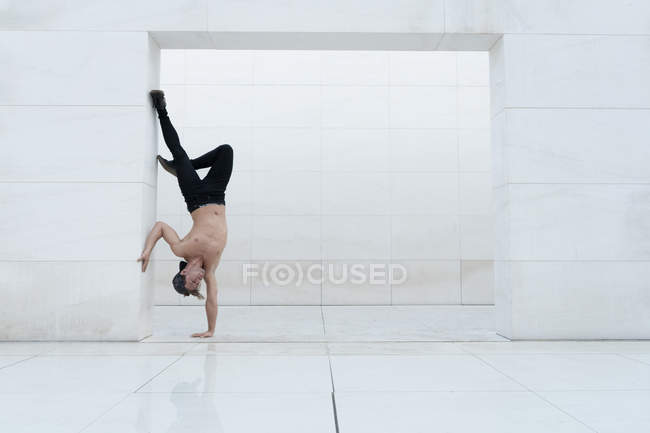 Shirtless muscular man performing one handstand in doorway of white studio room. — Stock Photo