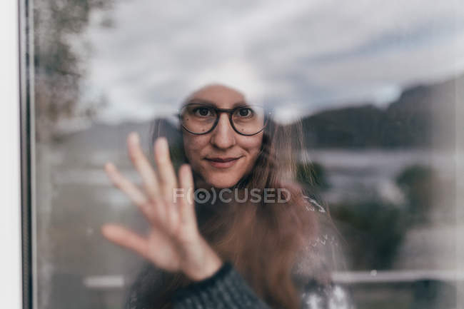 Portrait of woman wearing glasses and white hat and touching glass behind window — Stock Photo