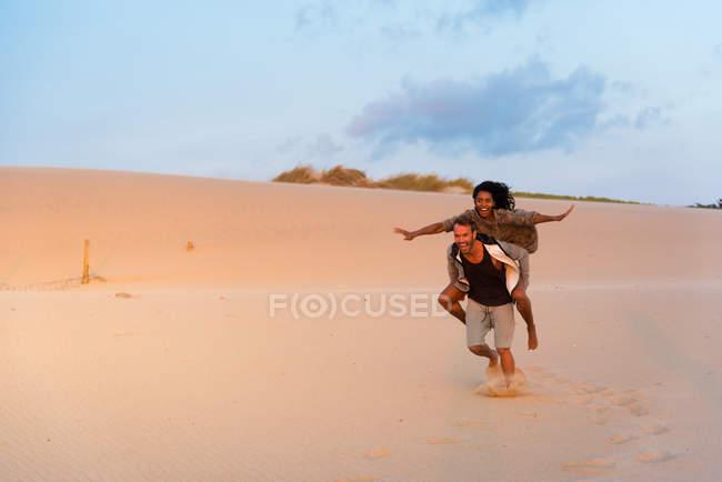 Lachen über Sanddünen auf Hintergrund geben Huckepack Freundin mit ausgestreckten Armen Mann — Stockfoto