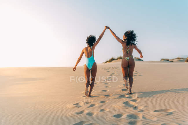 Rear view of women holding hands and walking in love on beach — Stock Photo