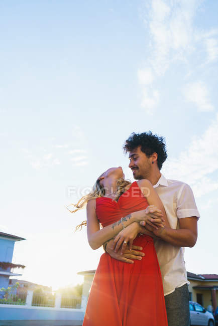 Low angle view of embracing couple looking at each other on sunny day — Stock Photo