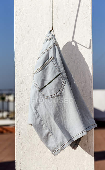 Blue jeans short hanging on terrace in sunlight — Stock Photo