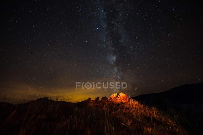 Illuminated tourist tent on hill on background of milky way in night sky — Stock Photo