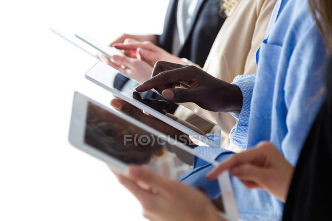 Crop of row of multhiethnic business people browsing tablets — Stock Photo