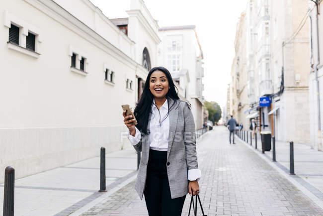 Retrato de mujer alegre caminando con teléfono en la calle - foto de stock