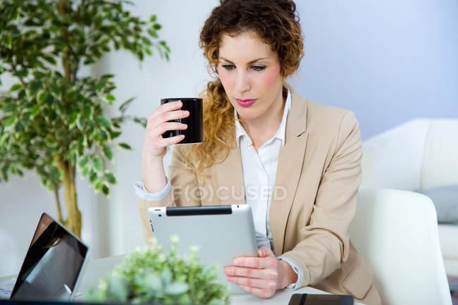 Porträt von Geschäftsfrau mit Tasse Kaffee mit Tablet im modernen Büro — Stockfoto