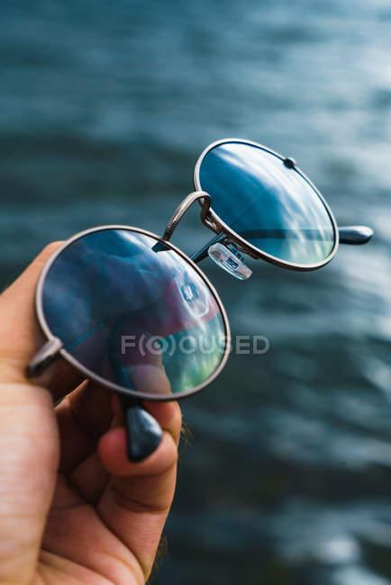 Mão de colheita segurando óculos de sol refletindo céu azul sobre ondas do mar — Fotografia de Stock