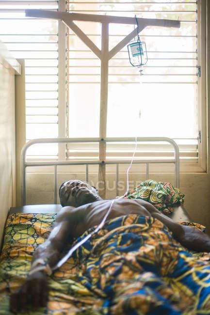 BENIN, ÁFRICA - 30 DE AGOSTO DE 2017: Homem negro deitado na cama com garrafa no hospital e olhando para a câmera — Fotografia de Stock