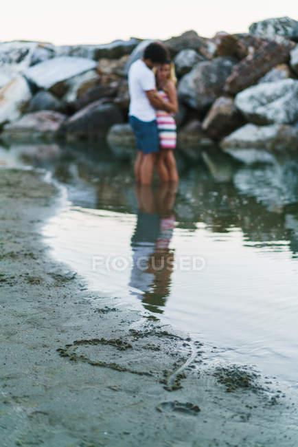 Mano dibujar corazón a orilla del mar mojado sobre pareja abrazándose en backgriound - foto de stock