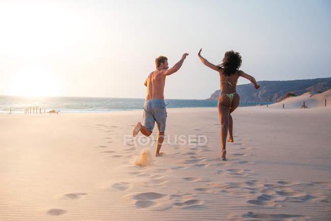 Vista posteriore della coppia in esecuzione sulla spiaggia tropicale romantica e dando il cinque — Foto stock