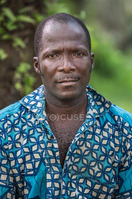 BENIN, ÁFRICA - 31 DE AGOSTO DE 2017: Retrato del hombre con camisa azul colorida mirando a la cámara . - foto de stock