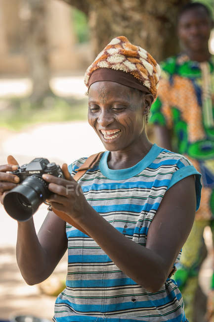 BENIN, AFRICA - AUGUST 31, 2017: Smiling ethnic african woman with camera — Stock Photo