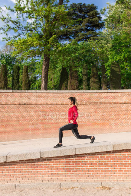 Side view of young woman in sportswear warming up legs at city park — Stock Photo
