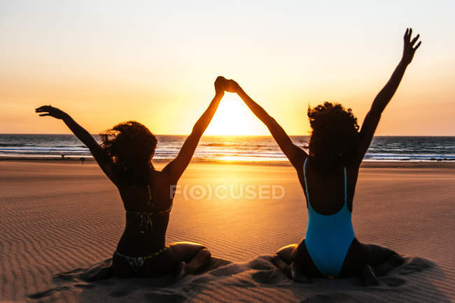 Rear view of women sitting on tropical beach and holding hands up over sunset sky — Stock Photo