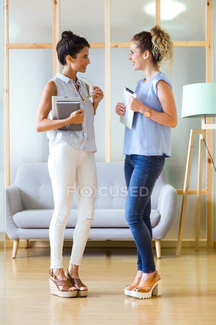 Портрет двух деловых женщин говорить в офис сцены — стоковое фото