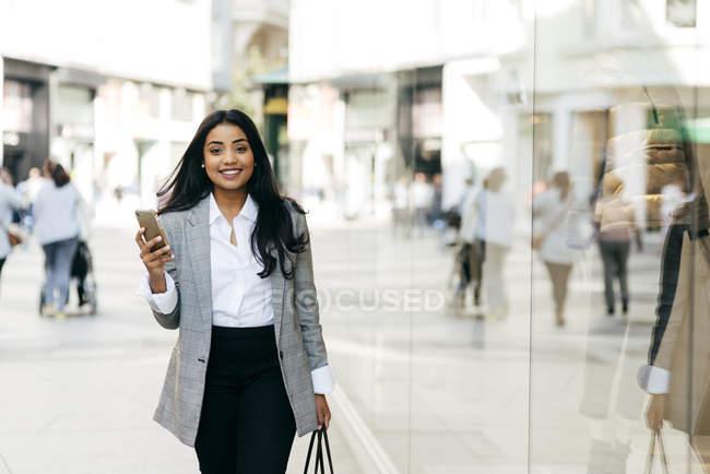 Vue de face de femme élégante avec smartphone marchant à côté des vitrines et regardant la caméra — Photo de stock