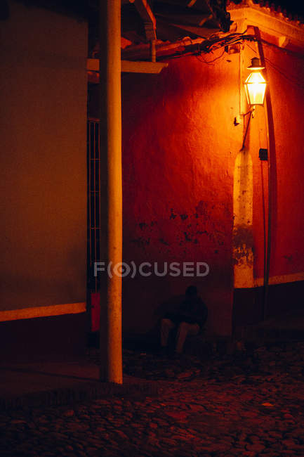 CUBA - AUGUST 27, 2016:Man sitting no ground in red light of lamp burning on corner of stone building — Stock Photo
