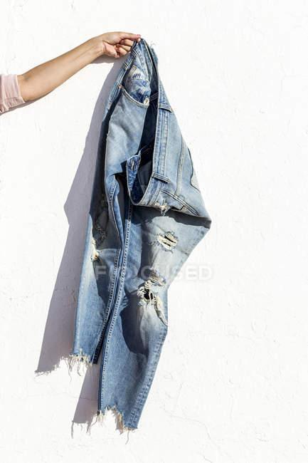 Mão de corte segurando jeans azuis sobre terraço iluminado pelo sol — Fotografia de Stock