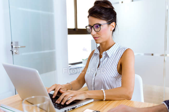 Portrait of  businesswoman working with laptop in modern office. — Stock Photo