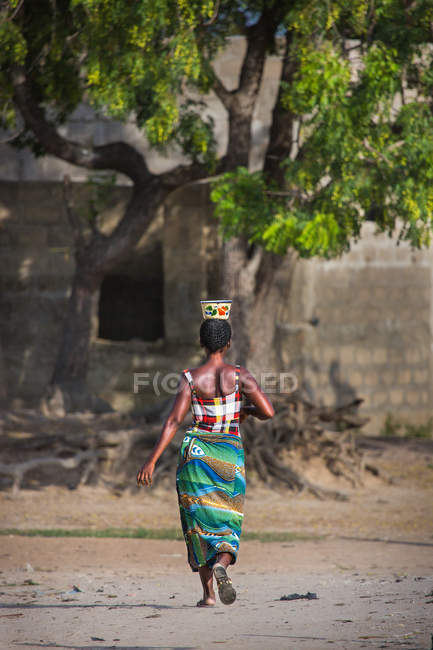Rear view of tribal woman walking with bowl on head at vilage — Stock Photo