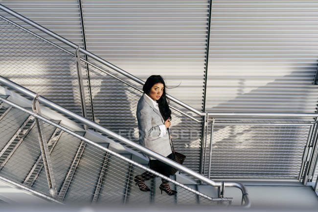 High angle view of elegant woman walking down stairs and looking at camera — Stock Photo