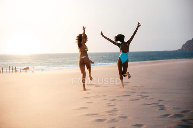 Vista posteriore della donna running allegramente sulla spiaggia tropicale — Foto stock