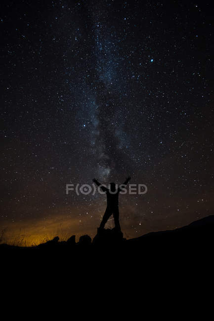 Silhouette of man posing with arms raised under the milky way — Stock Photo