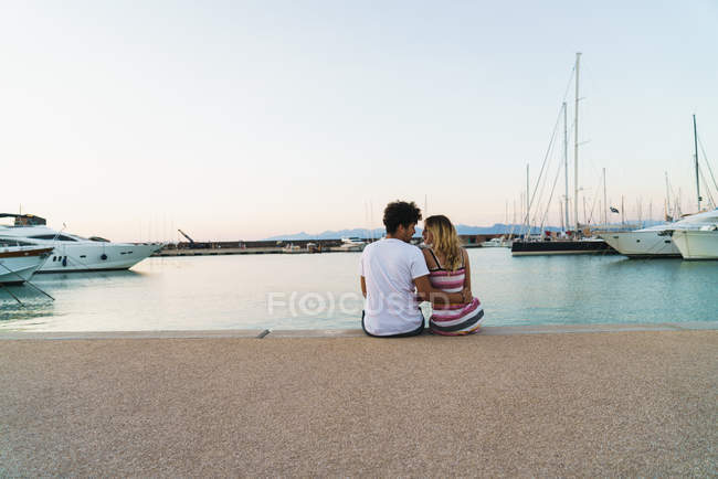 Rear view of couple embracing on pier with moored yachts — Stock Photo