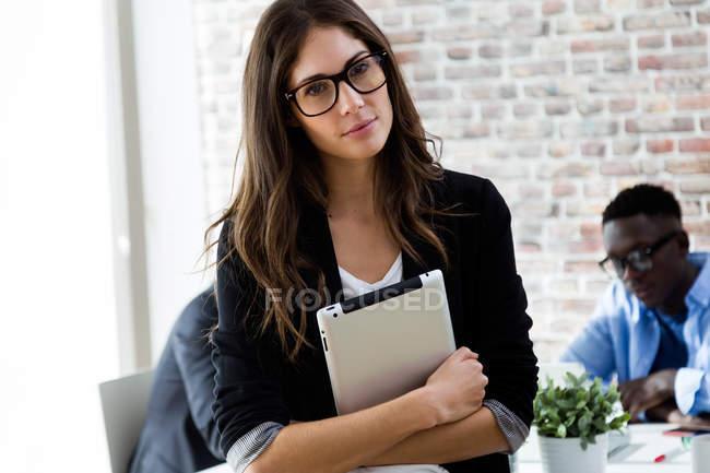Портрет підприємець, підтримуючи планшет і дивлячись на камеру в офісі лофт — стокове фото